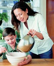 "This photo provided by Potter shows chef-caterer Debra Ponzek cooking with her son Cole Addonizio. The photo is from ""The Family Kitchen,"" Ponzek&squot;s cookbook with recipes for parents and children ""to make and enjoy together."""