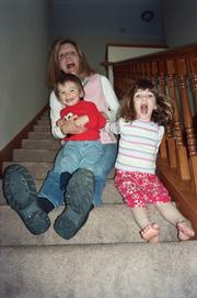 Journal-World copy editor Susie Fagan and her children, Max, nearly 2, left, and Erin, who turns 4 today, horse around on the stairs at the family's home.