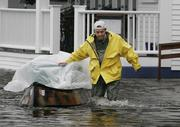 A York Beach, Maine, resident escorts a canoe filled with belongings through a flooded street outside his house. Torrential rain washed out roads and forced some people from their homes early Sunday.