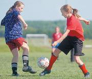 Weasels player Cailin Caldwell, right, makes a move past a Wizards defender. The Wizards defeated the Silly Willy Weaels 2-0 Saturday at Youth Sports Inc.