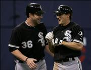 Chicago White Sox's Chris Widger, left, celebrates a second inning two-run home run by Scott Podsednik, right, off  Minnesota Twins' Scott Baker in a baseball game Monday, May 15, 2006 in Minneapolis.  Widger went 3 for 5 with two runs and 3 RBI as the White Sox beat the Twins 7-3.