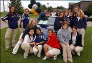 Members of the Bishop Seabury Academy senior class surround a 1995 Ford Thunderbird, donated to the school for Project Graduation. Students in the senior class who attend the party that starts Sunday night and ends early Monday will have a chance to win the vehicle.