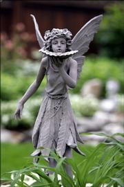 A fairy statue is part of the decor in Pam Borchardt's backyard. The Borchardts have created a whimsical woodland habitat at their Lawrence home.