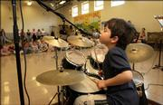 "Five-year-old Robbie Matthews beats away on a miniature drum set as he sings ""Wild Thing"" on Wednesday at East Heights Early Childhood Center, 1430 Haskell Ave. He also performed several Beatles songs for his school friends in a band with his father, Paul Matthews, on piano; Doug Byers on guitar; and East Heights custodian James ""Mr. T"" Thomas on bass. Robbie has been interested in drums since he was 10 months old."