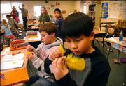 Sunflower School fifth-graders Jack Shin, front, Cole Cummins and other students in Kristy Kopp's science class assemble miniature helicopters with corks and feathers as a part of an experiment measuring the rate of the helicopter's fall relative to the number of feathers attached. The Lawrence metro area ranks third in the country for the quality of its public schools, according to a new study from Expansion Management magazine.