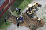 Workers dig near a barn at a horse farm in Milford Township, Mich., where FBI agents investigating Jimmy Hoffa's 1975 disappearance were working for a second day Thursday. The Teamsters leader had vanished from a restaurant in Bloomfield Township, about 20 miles away.