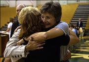 Free State High School english teacher Mary Chapman, right, hugs her sister Madeline Raile, St. Louis, back left, and niece Kim Smith, St. Louis, front, after receiving the Bobs' Award at an assembly in the school gym. The annual prize, a $10,000 check from the Lawrence Schools Foundation, is given in recognition of teaching excellence.