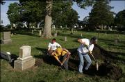A crew digs up a grave at Oak Hill Cemetery in hopes of solving a 19th century mystery that led to a federal rule on hearsay evidence. Two Colorado professors spearheaded the dig. The exhumation crew includes, from left, Sarah Garner, Paul Sandberg and Ben Herr.