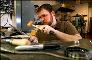 Kansas University senior Blaine Carver-Allmond, of Pittsburg, hammers away on a sterling silver ring Friday afternoon in the workshop of the Art and Design Building. Carver-Allmond will feature his jewelry in the KU Senior Art Show today.