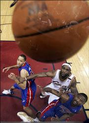 Detroit's Tayshaun Prince, left, and Lindsey Hunter, right, battle Cleveland's LeBron James for position on a rebound. The Pistons defeated the Cavaliers, 84-82, Friday night in Cleveland to even their series at three games apiece.