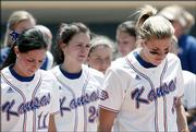 Dejected Kansas University softball players wait to congratulate their Washington counterparts after the Huskies' 3-0 victory. KU was ousted from the NCAA Tournament on Saturday in Provo, Utah.