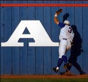 Kansas University's John Allman catches a fly ball at the warning track in left field in the sixth inning of the Jayhawks' 6-2 victory over Texas A&M. KU won Saturday at Hoglund Ballpark.