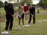 Randy Towner lets a ball fly at the chipping range as his students attempt to emulate him.
