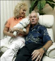 Former daredevil Evel Knievel sits with longtime partner Krystal Kennedy-Knievel and their dog, Rocket, in their condo May 11, 2006, in Clearwater, Fla. Evel Knievel, a 1970's cultural icon and poster boy for fast living and derring-do, has trouble now just walking from his condo to the pool. His 67-year-old body is broken by years of spectacular crashes and ravaged by a multitude of serious ailments.