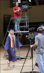 Montgomery Central High School graduate Rebecca Brit walks between cameras being used to broadcast the graduation in Clarksville, Tenn. Seven high schools near Fort Campbell, the home of the Army's 101st Airborne Division, are broadcasting their graduation ceremonies live online for family members stationed overseas. Montgomery Central's ceremony was Friday.