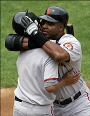 San Francisco Giants slugger Barry Bonds, right, embraces his son, Nikolai, after hitting his 714th career home run. Bonds tied Babe Ruth for second on the all-time career home run list Saturday in Oakland, Calif.