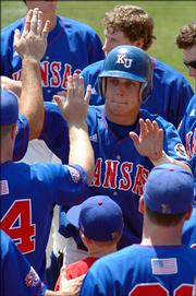 KU's John Allman is congratulated by his teammates after scoring in the third inning. Kansas plated seven runs in the inning to put away Texas A&M.