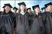 Singing the Lawrence High School Alma Mater, front row from left, are graduating seniors Sharie Barnard, Marissa Ballard and Rebecca Ball. Lawrence High School's 132nd commencement was Sunday at Haskell Stadium.