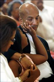 Tianna Nagin wipes a tear on the face of her father, New Orleans Mayor Ray Nagin, as they attend mass at St. Peter Claver Catholic Church in New Orleans. At left Sunday is Nagin's wife, Seletha.