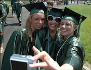 Free State high school seniors, from left, Tricia Dunham, Christina Bernhardt and Jessica Stuart take a picture of themselves during graduation. The school's ninth commencement was Sunday at Haskell Stadium.