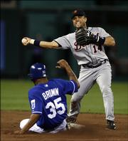 Detroit second baseman Placido Polanco prepares to throw over Kansas City's Emil Brown to complete a double play. The Tigers won, 8-0, on Monday night in Kansas City, Mo.