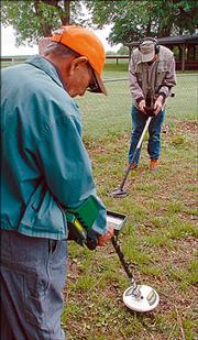 Delmar Motycka and Tom Thiessen, in background, use metal detectors while searching for bullets at the Black Jack Park. The team from Lincoln, Neb., failed to find any new artifacts from the site.