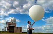 National Weather Service meteorologist intern Gordon Strassberg, Topeka, prepares to launch a weather balloon equipped with a transmitting device Tuesday at the National Weather Service station in Topeka. Although forecasting technology has improved greatly in the 40 years since a tornado caused massive damage in Topeka, balloons still are used to collect information from the upper atmosphere and play a key role in forecasts.