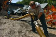 Brian Barney hooks up a hose that will deliver 8,000 gallons of gas to the Presto Phillips 66 gas station, 602 W. Ninth St. Barney worked Tuesday at the station, which is expected to reopen in about two weeks. It has been closed since an April 30 fire at a nearby house.