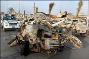 A U.S. soldier in a Humvee, right, and an Iraqi policeman, left, examine the wreckage of a vehicle containing a car bomb that detonated in the late afternoon outside a police station in Sadr City, a sprawling Shiite district in northeast Baghdad, killing five. The bombing was one of several Tuesday that left at least 40 Iraqis dead.