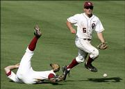 Oklahoma's Russell Raley, left, falls down as teammate Kody Kaiser scrambles for the ball during the second inning of the Sooners' Big 12 tournament game against Kansas. The Jayhawks earned a 7-2 victory Wednesday in Oklahoma City.