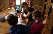 Lawrence mother of four and homeschooler Karen Flory gives her oldest son, Weston, 9, right, a phonics lesson as her second oldest boy, Tucker, 5, sits Tuesday at their home. Weston is completing his first full year of the Lawrence Virtual School, which allows his mother to teach a curriculum of six subjects. Tucker will be enrolling in the Virtual School in the fall.