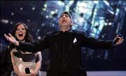 "Taylor Hicks reacts after being announced the winner of season five of ""American Idol."" Pictured in the background Wednesday is runner-up Katharine McPhee."