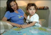 "At 2 1/2 years old, Tavi Shaffer-Green looks for Easter Island on a world map with his mother, Tanya Shaffer. Tavi can pick out every country on a world map, including Togo, which he likes because of its tiny size. Tavi also is the son of David Green. Shaffer is a Lawrence High School graduate, and her father, Harry Shaffer, is a longtime economics professor at Kansas University. Green was the recipient of the MacArthur Fellowship - or ""genius award"" - in 2004."