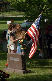 Girl Scout Paula Kyriakos, 16, holds a flag during the annual Alfred Bromelsick Memorial Saturday in Oak Hill Cemetery. Scouts and 4-H members attended a service for Bromelsick, a Lawrence businessman who left his estate to youth groups.