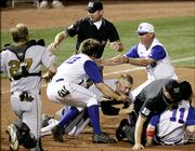 Third-base umpire Doug Williams, center rear, and home-plate umpire Chris Coskey try to get between Missouri's Brock Bond and Kansas' Ryne Price (11) during a second-inning fight that started when Price and Bond collided after Price homered. Both were ejected.