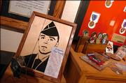 Jim and Cindy Butler have dedicated a wall in their home to memorialize their son. Among some of the items are his wartime medals, including the Purple Heart, dog tags, photographs and a wood carving of his military portrait.