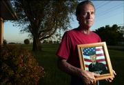 Wellsville resident Jim Butler holds a military portrait of his son, Sgt. Jake Butler, who was the first Kansas soldier killed while serving with the Army in Samawa, Iraq, on April 1, 2003. A little more than six months after his son's death, Butler made a journey to Samawa to visit the site where Jake was killed near the Euphrates River.