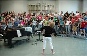 After 31 years in Lawrence Public Schools, Free State High School vocal music director Pam Bushouse is retiring. Bushouse leads a choral class at FSHS in some stretching exercises before a rehearsal.