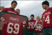 Mitchell McGinnis, left, holds the framed jersey of his best friend, Lucas Frantz, who played football for Tonganoxie High School. McGinnis, along with other members of Frantz's high school team, honored Frantz by retiring his jersey before an Oct. 21, 2005, game against De Soto. Frantz's wife, Kelly Frantz, second from right, wore Frantz's number.