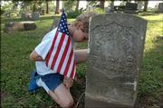 Anthony VanSchmos, 9, of Cub Scout Pack 3052 places a flag on a Civil War veteran's grave on Saturday in Oak Hill Cemetery.  The Scouts joined members of the Sons of Civil War Veterans to decorate graves of Civil War veterans.