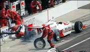Sam Hornish Jr. leaves his pit stall with the fuel nozzle still attached as a crewman, just to the left of the car, falls to the pavement during the Indianapolis 500. Despite the mishap, Hornish won the Indianapolis 500 on Sunday in Indianapolis.