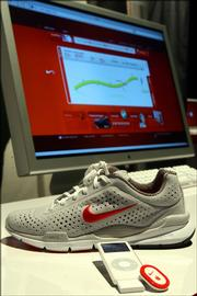 The Nike Air Zoom Moire is pictured alongside an iPod, the Nike+iPod Sport Kit and a computer screen displaying the Nikeplus.com Web site.