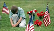 A young boy bows his head during the invocation of the Dorsey-Liberty Post No. 14 American Legion Memorial Day service at Oak Hill Cemetery. The American Legion was able to have its service before rain moved in Monday morning.