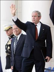 President Bush waves after speaking at Arlington National Cemetery Memorial Day commemoration. He and Defense Secretary Donald Rumsfeld attended the ceremony just a short time after Bush signed into law a bill that restricts protests at military funerals.