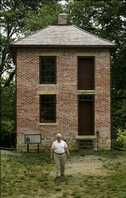 Shawnee County Historical Society trustee Bill Wagnon walks away from the partially restored John Ritchie house in Topeka.