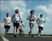 Lawrence artist Stan Herd, second from left, and his son Evan, 14, second from right, embark on a 12-day, 100-mile run from Lawrence to the Flint Hills. Herd started Monday morning near Clinton Lake  with, from left, Chris Ford, Allen Levine and Steve Dinneen.
