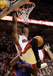 Miami's Dwyane Wade hangs onto the rim after dunking against the Detroit Pistons. The Heat won Game 4, 89-78, Monday in Miami.