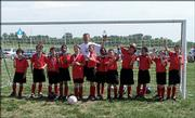 The Elite pose for a team picture with Coach Murray after capturing the 10U Division 1 Classic Clup title May 20.