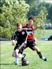 U11 KVSA Force player Gavin Fischer shields the ball from a forward from the KC Legends WCI at the Kansas City Invitational Tournament on Saturday.