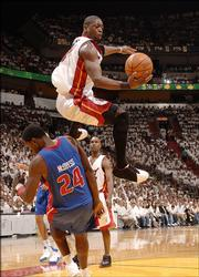 The Miami Heat's Dwyane Wade, top, goes up for a shot over the Detroit Pistons' Antonio McDyess. Wade scored and drew a foul on the play during Game 4 of the Eastern Conference finals Monday in Miami.